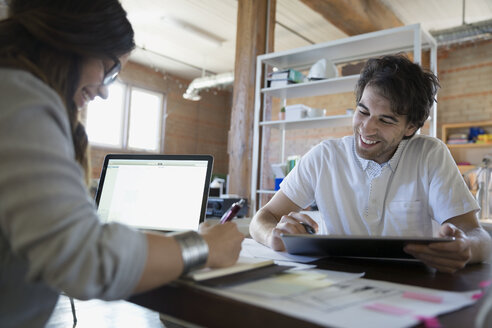 Designers with laptop and digital tablet discussing plans in office - HEROF34248