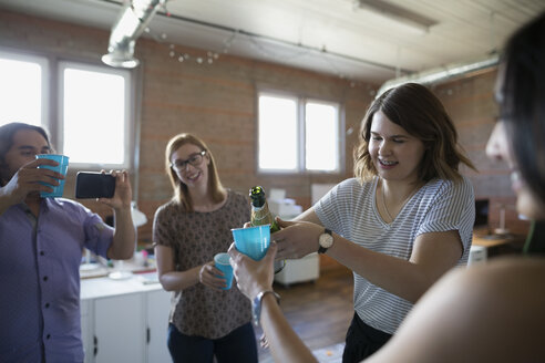 Creative business people celebrating pouring champagne in office - HEROF34281