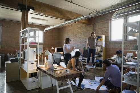 Designer standing on chair looking down at proofs and paperwork on office floor - HEROF34287