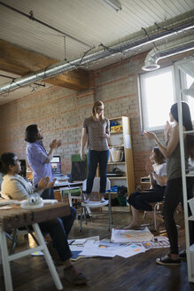 Coworkers clapping for designer standing on chair in office - HEROF34290