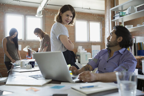 Designers talking at laptop in office - HEROF34299