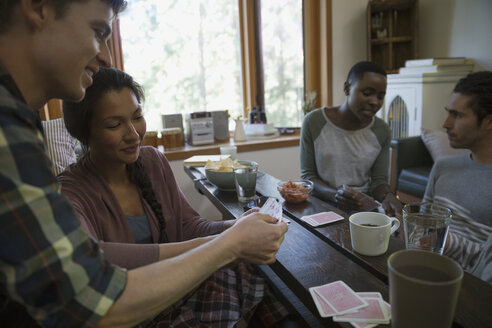 Couples playing cards in living room - HEROF34347