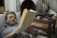 Comfortable man relaxing reading book in living room - HEROF34353