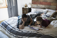 Comfortable homosexual couple using digital tablet and cell phone on bed - HEROF34356