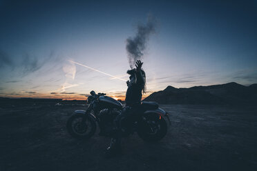 Bearded man with dreadlocks sitting on motorbike at sunset smoking electronic cigarette - OCMF00352