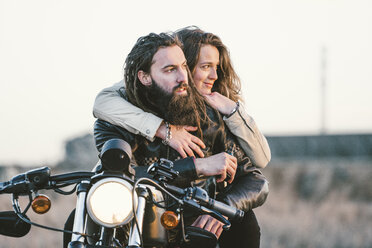 Portrait of couple on motorbike looking at distance - OCMF00355