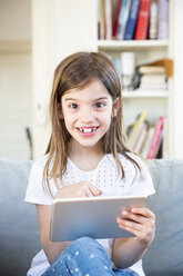 Portrait of happy little girl sitting on the couch at home using digital tablet - LVF07956