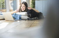 Happy young woman with dog lying at the window at home shopping online - UUF16992
