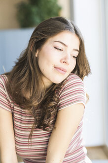 Portrait of young woman at home daydreaming - UUF16998