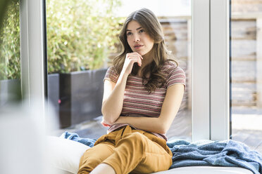 Pensive young woman sitting at the window at home - UUF17004