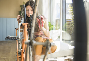 Young woman reparing bicycle at home - UUF17016