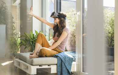 Young woman sitting at the window at home wearing VR glasses - UUF17022