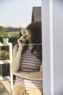 Portrait of pensive young woman behind windowpane - UUF17028
