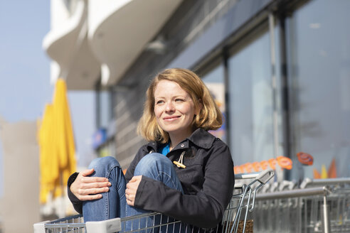 Portrait of smiling woman sitting in shopping cart in front of supermarket - SGF02352