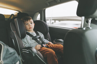 Little boy sitting in car on child's seat with fastened seat belt - CMSF00001
