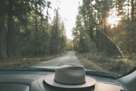 Car driving through forest with hat on dashboard - CMSF00007