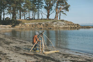 Boy playing on a the beach, building a drift wood fort - CMSF00019