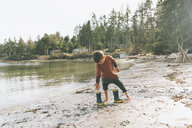Boy playing on a the beach, walking barefoot in the mud - CMSF00022