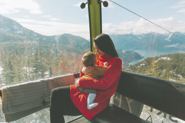 Mother holding her baby son in the gondola of a cable car, Squamish, Canada - CMSF00025