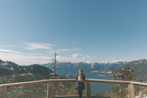 Mother holding her baby son on an observation deck, looking over Squamish, Canada - CMSF00031