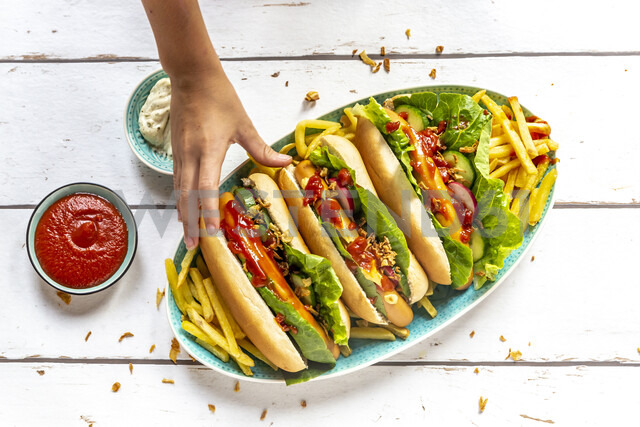 Hot dogs with french fries, ketchup and mayonnaise, hand taking an hot dog - SARF04211 - Sandra Roesch/Westend61