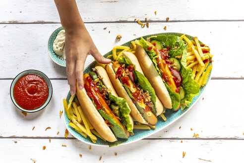 Hot dogs with french fries, ketchup and mayonnaise, hand taking an hot dog - SARF04211