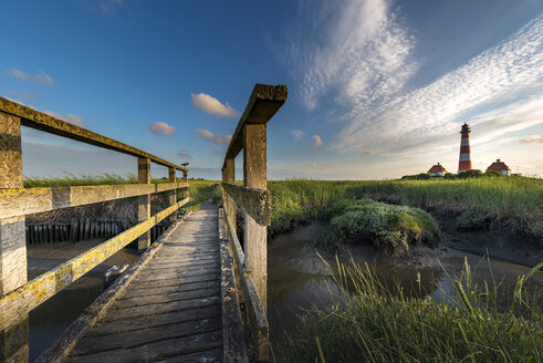 Germany, Westerhever, wooden bridge and lighthouse in sunset - MKFF00482