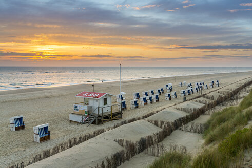 Germany, Sylt, North Sea, sandy beach with hooded beach chairs in sunset - MKFF00485