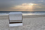 Germany, Sylt, North Sea, sandy beach with hooded beach chair in sunset - MKFF00488