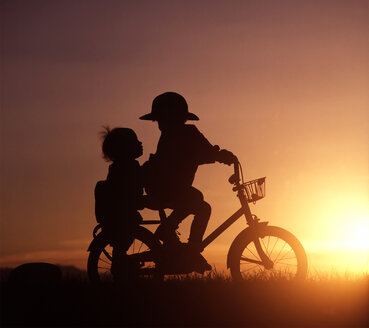 Silhouette of two children riding bicycle in sunset - WWF04913