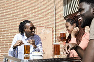 Three happy friends drinking beer at an outdoor bar - IGGF00951