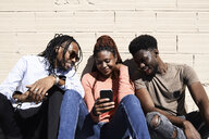 Three friends sitting together and watching a video on a smartphone outdoors - IGGF00960