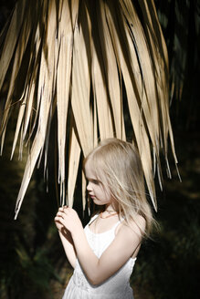 Little girl in white dress at a palm tree - EYAF00101