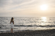 Little girl in white dress looking at sunset over the sea - EYAF00116