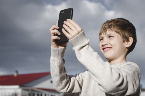 Portrait of happy boy taking selfie with smartphone - EYAF00122