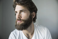 Pensive bearded brunette man looking away - HEROF34388