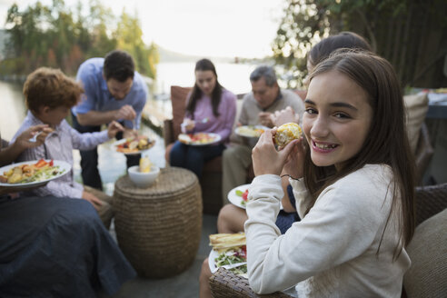Portrait smiling girl eating with family on patio - HEROF34439