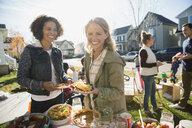 Portrait smiling neighbors enjoying potluck sunny front yard - HEROF34454