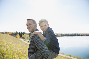 Portrait father piggybacking son in sunny field - HEROF34475