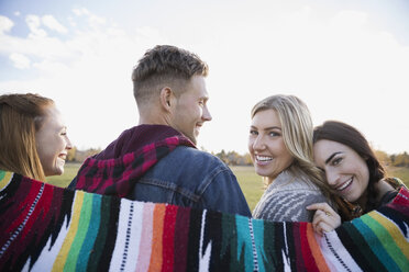 Portrait smiling friends wrapped in a blanket - HEROF34478