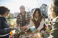Neighbors enjoying potluck in sunny front yard - HEROF34538