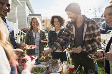 Neighbors enjoying potluck in sunny front yard - HEROF34541
