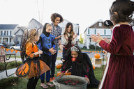Kids in Halloween costumes bobbing for apples - HEROF34553