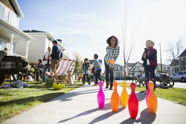 Kids bowling on sunny neighborhood sidewalk - HEROF34559