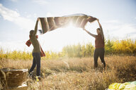 Mother and daughter shaking picnic blanket in sunny field - HEROF34565