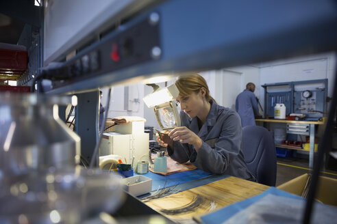 Worker examining part with magnification glass in factory - HEROF34595