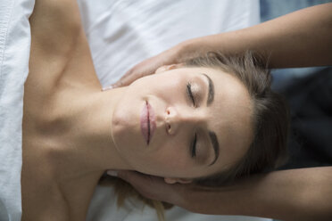Serene woman with eyes closed receiving head massage - HEROF34673
