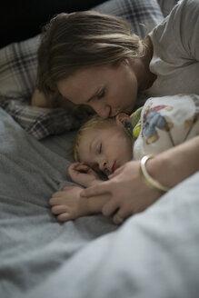 Mother cuddling sleeping son in bed - HEROF34700
