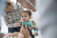 Pediatrician examining baby with stethoscope in examination room - HEROF34703