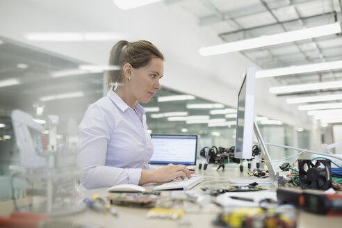 Engineer working at computer with robotics - HEROF34820